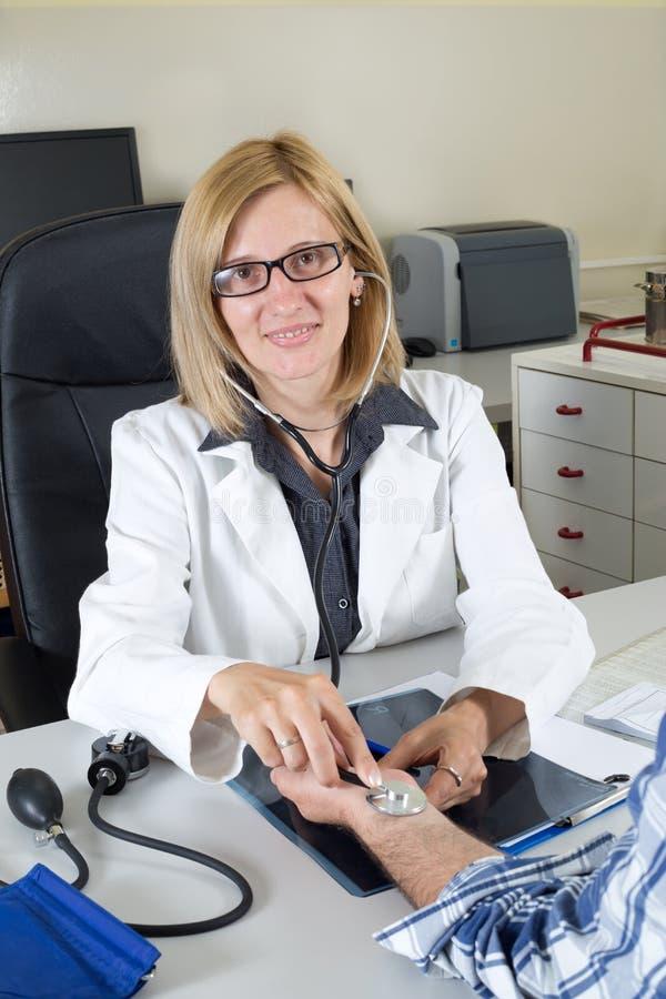 Tension artérielle de mesure femelle de sourire de docteur With Accessories For photographie stock