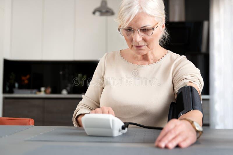 Tension artérielle de mesure de femme adulte supérieure images stock