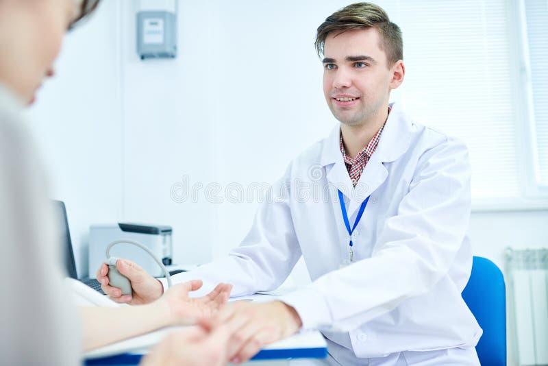 Tension artérielle de mesure de jeune docteur images libres de droits