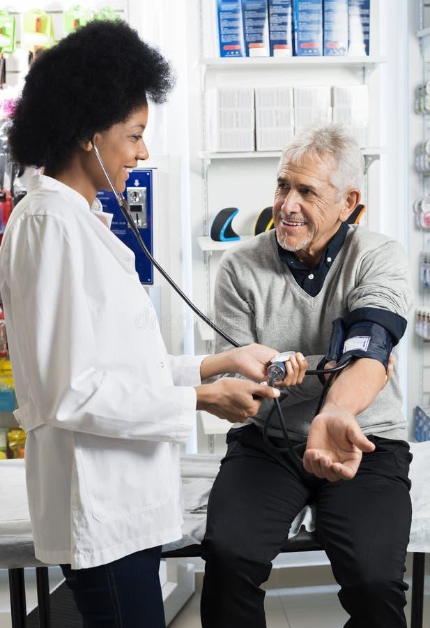 Tension artérielle de sourire du ` s de Checking Patient d'infirmière photo libre de droits