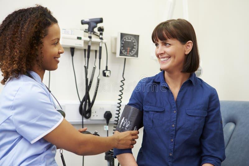 Tension artérielle de Taking Female Patient d'infirmière dans l'hôpital photos stock