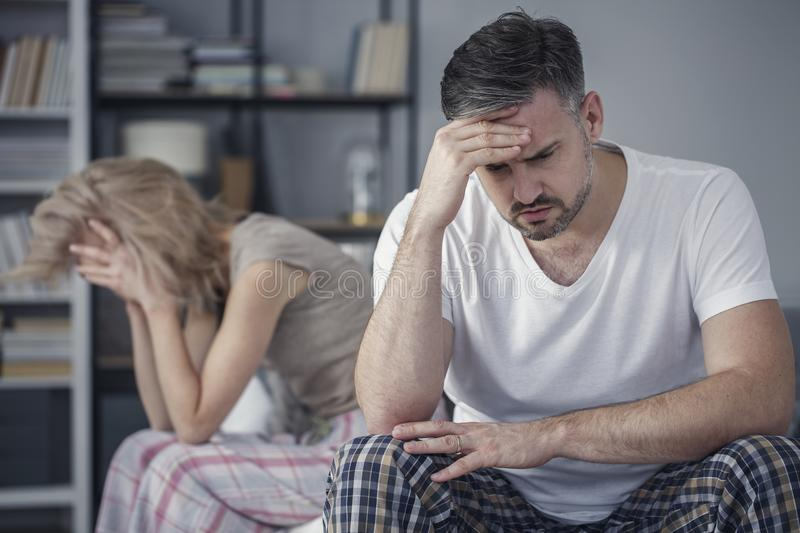 Tension between distant married couple. Tension between a distant married couple with relationship problems with focus on the husband in the foreground royalty free stock photos