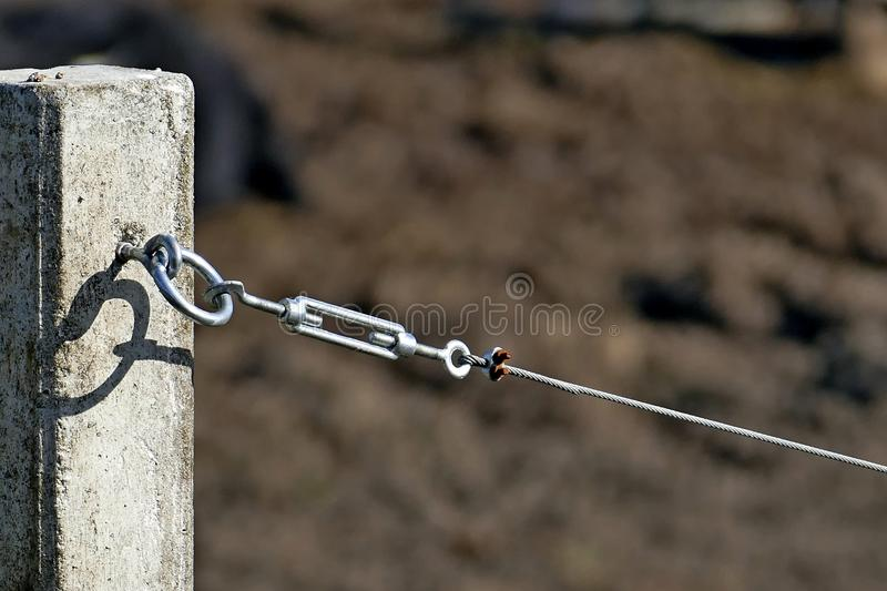 Tension hook with wire rope. Stretched on a concrete bar royalty free stock images