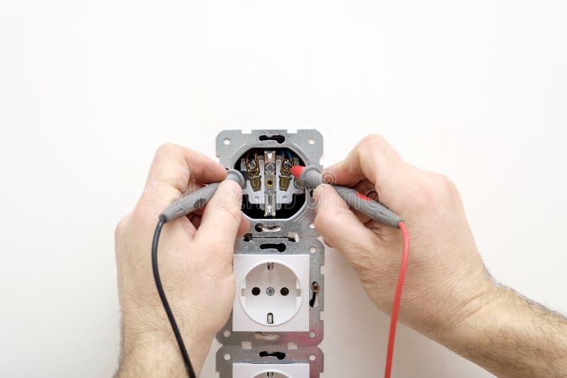 Tensione di misurazione dell'elettricista nello sbocco facendo uso di un multimetro in mani immagini stock libere da diritti