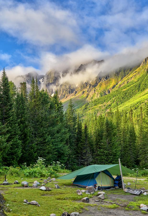 Tent backpackers installed on edge of dark forest stock image