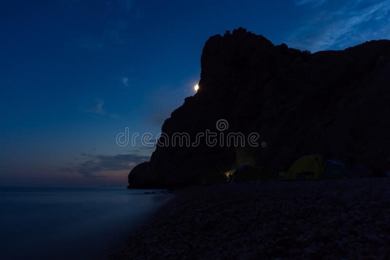 Tent on the beach at night. Full moon over the mountain. Outdoor recreation. Night seascape. Traveling with tents. Summer vacation on the shore of the night stock image