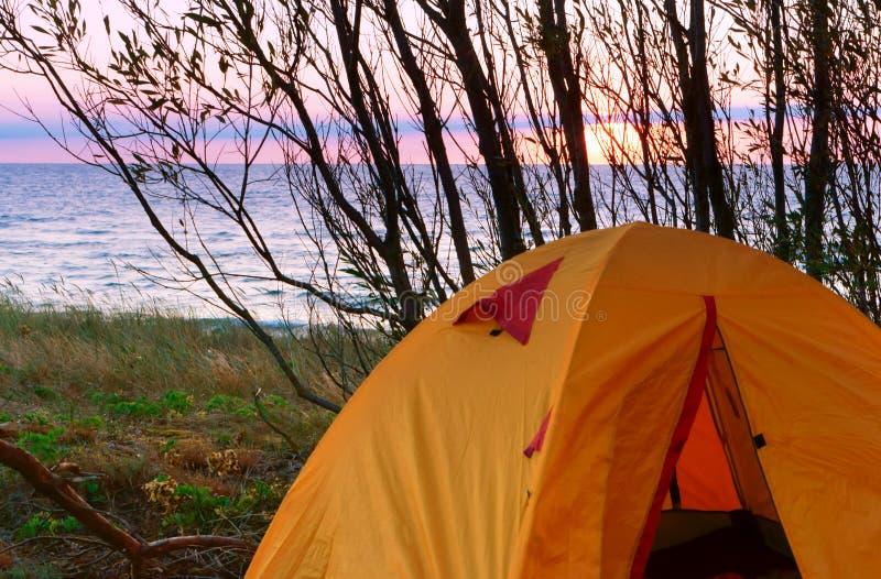 Tent bij zonsondergang op het overzees, toeristentent op het strand stock afbeeldingen