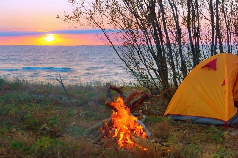 Tent en brand bij zonsondergang op het overzees, toeristentent op het strand royalty-vrije stock foto's