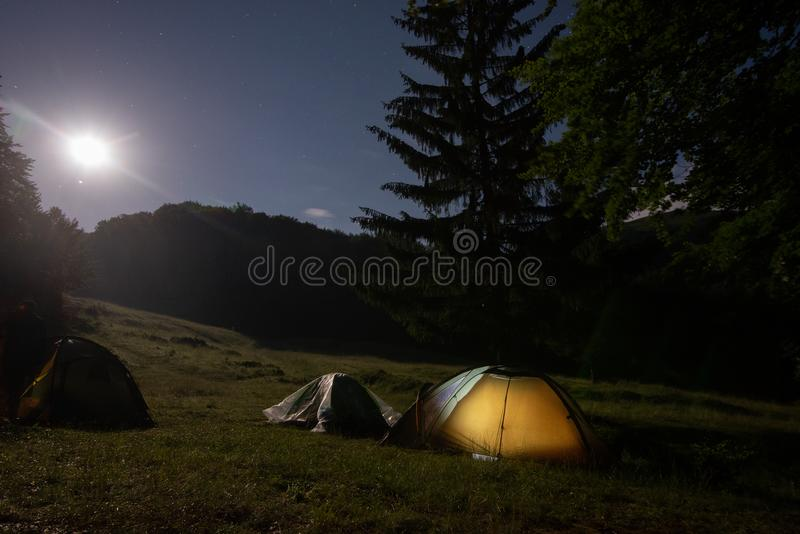 A tent glows under a night sky full of stars. royalty free stock photos