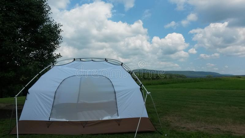 Tent in the grass mountain stock images
