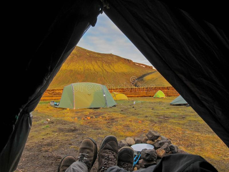 Tent lookout with couple hiking boots and mountain view at sunset, Nature reserve, highlands of iceland. Tent lookout with couple hiking boots and mountain view stock photo