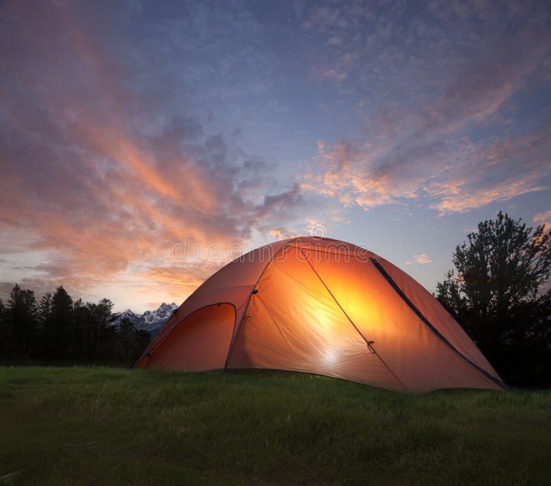 Tent met licht binnen bij schemer dichtbij de bergen van Grand Teton stock fotografie