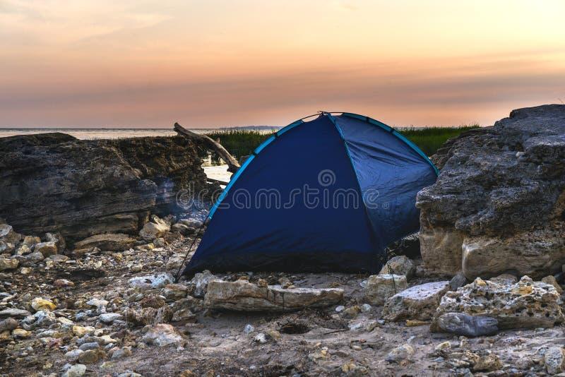 Tent op het steenstrand van het overzees De tijd van de zonsondergang stock foto