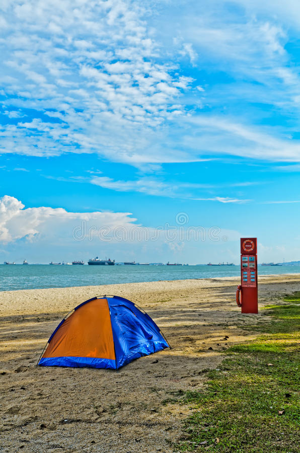 Tent on picturesque beach. Scenic view of colorful tent on picturesque beach with sea, blue sky and cloudscape background royalty free stock photos