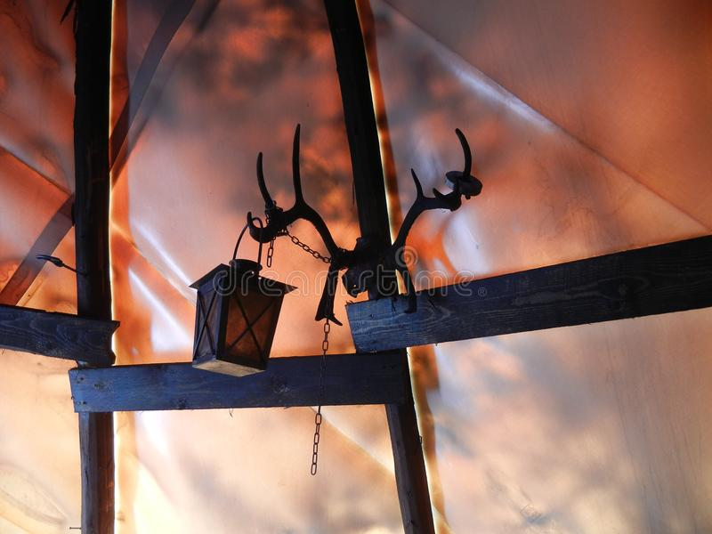 Tent with reindeer antlers and a lantern. Inside of a tent in Sipoonkorpi National Park in Finland. Reindeer antlers attached to the wooden beams serving as a stock photo