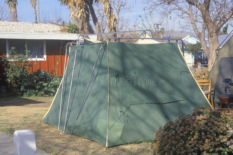 A tent set up in a yard housing people