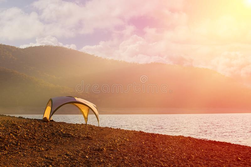 Tent shelter on lake shore at sunset - tranquil scene conveying calmness and freedom. Tent shelter on lake shore at sunset - tranquil scene conveying calmness royalty free stock photography