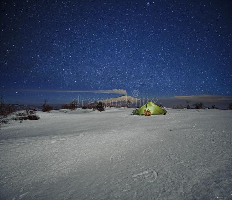 Tent In The Snow And Etna Volcano Under Starry Sky. Illuminated tent in the snow and smoking Etna volcano view under starry sky from Nebrodi Park, Sicily royalty free stock photography