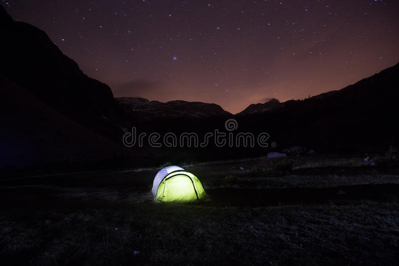 Tent standing on a mountain pasture under starry sky stock images
