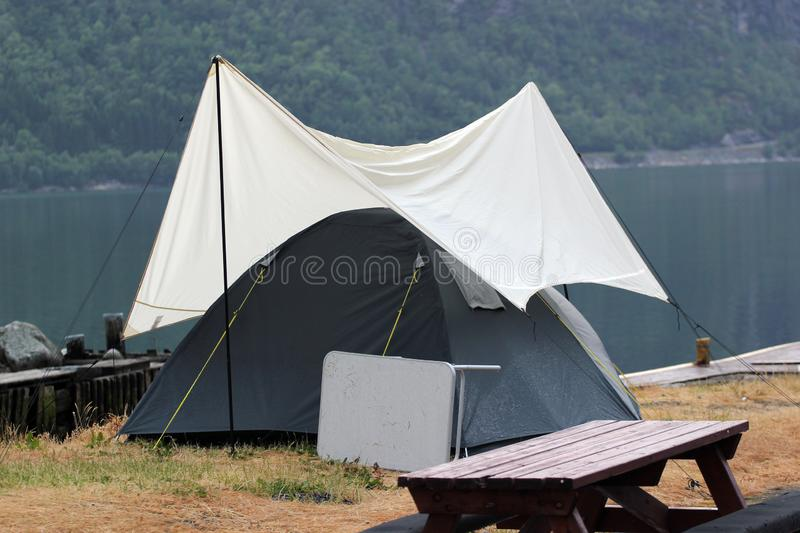 Tent under awning on a camping ground, Norway. Rainy weather at scandinavian fjords royalty free stock photography