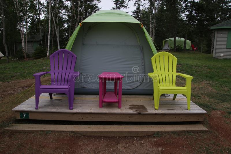 A tent on a wooden platform. With two chairs and a table sitting in front, color, design, green, nature, outdoor, park, pink, purple, summer, travel, yellow stock photos
