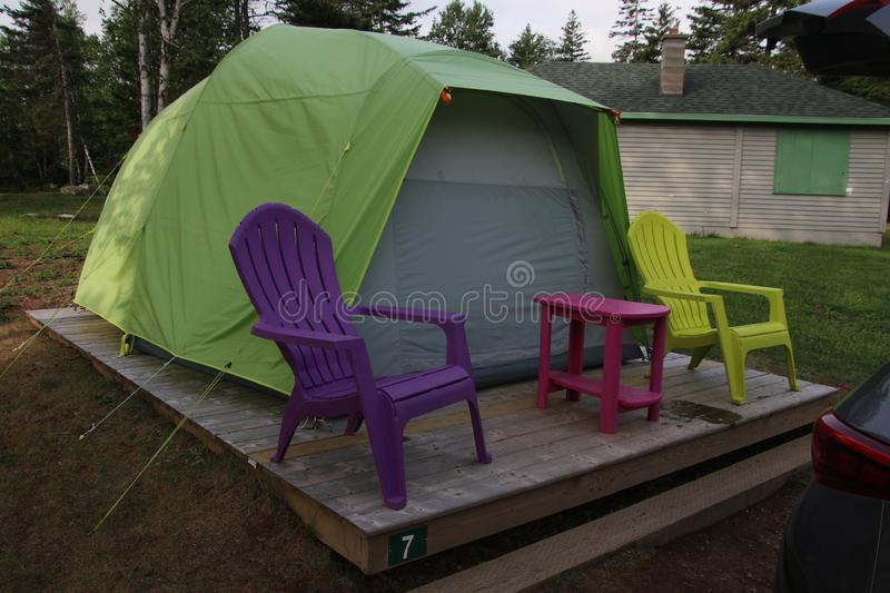 A tent on a wooden platform. With two chairs and a table sitting in front, color, design, green, nature, outdoor, park, pink, purple, summer, travel, yellow royalty free stock image