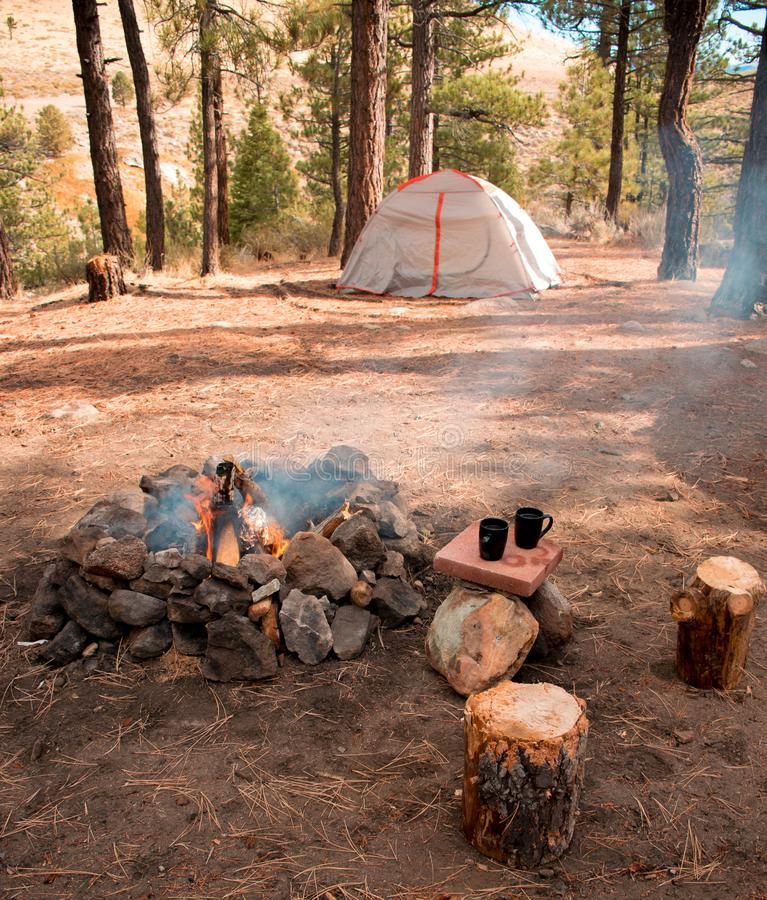 A tent in the woods with a small campfire and two coffee mugs stock photography