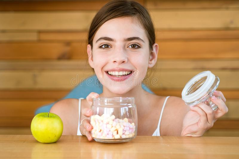Tentación dulce Azúcar o vitamina La mujer bonita prefiere melcochas a la manzana La mujer elige qué comida a comer Orgánico imagen de archivo