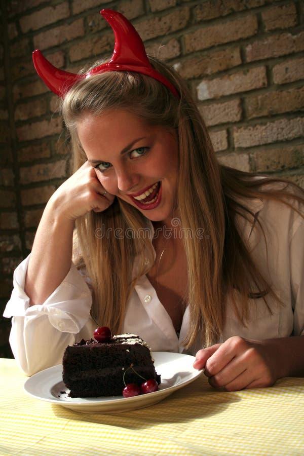 Tentation de diables de gâteau de chocolat du femme v image libre de droits