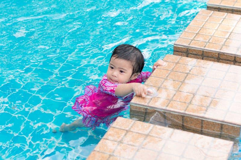 Tentativa asiática pequena da menina que nada apenas na piscina, exterior fotos de stock