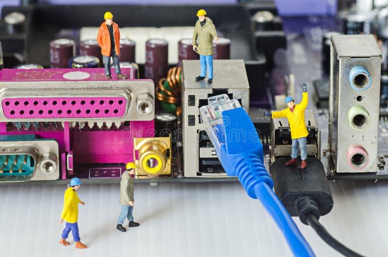Tentativa diminuta da equipe do coordenador para conectar cabos ethernet ao porto imagens de stock royalty free
