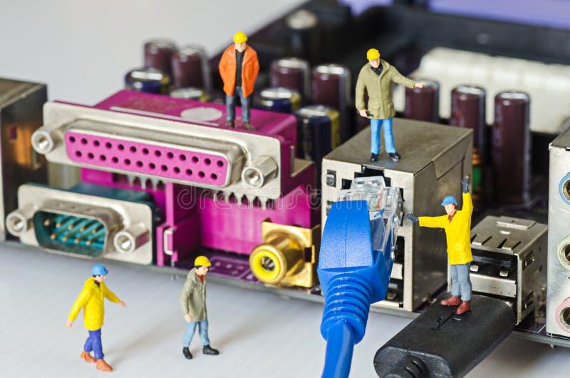 Tentativa diminuta da equipe do coordenador para conectar cabos ethernet ao porto fotografia de stock