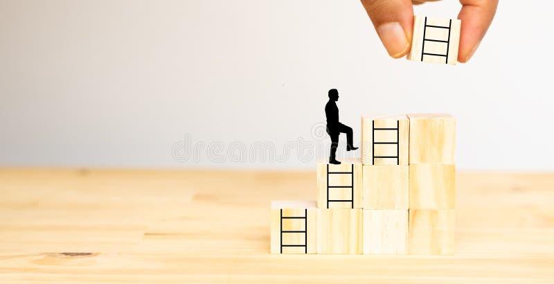 Tentativa do homem da mão para pôr a escada seguinte sobre os dados de madeira ao homem para o passo seguinte, possibilidade, tra fotografia de stock