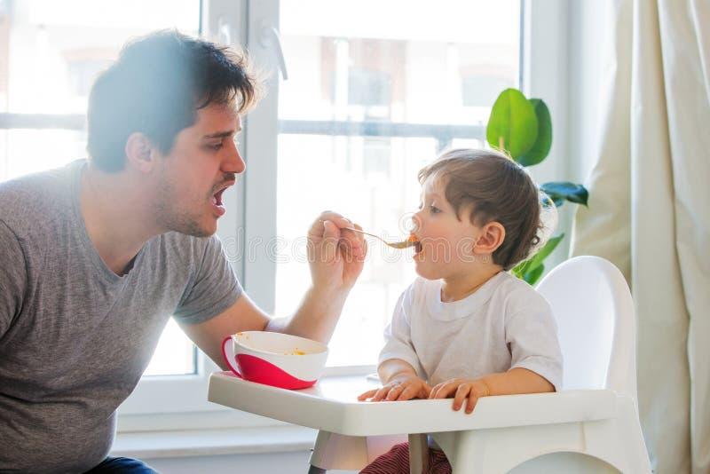 Tentativa do pai a alimentar um menino da crian?a com uma colher em uma cadeira fotos de stock royalty free
