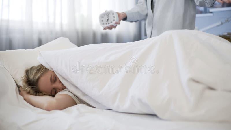 A tentativa inútil de acordar a filha na manhã, tarde para a escola, incomodou adolescente imagens de stock