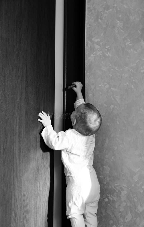 Tentativas do bebê para abrir a porta imagens de stock