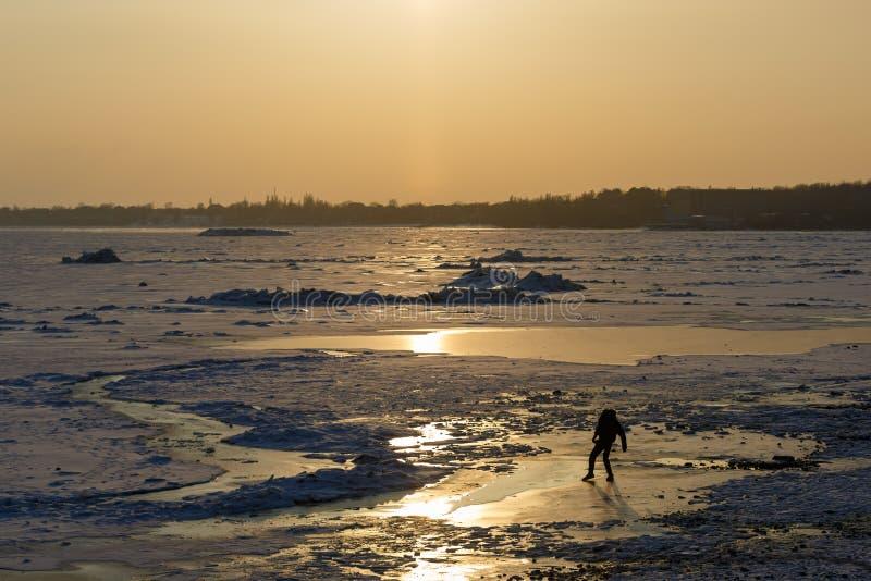 Tentativas do homem para passar sobre o gelo fino de um mar congelado em uma noite do inverno foto de stock