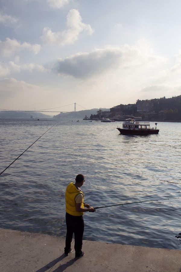 Tentativas do homem para travar peixes por Bosphorus imagem de stock royalty free