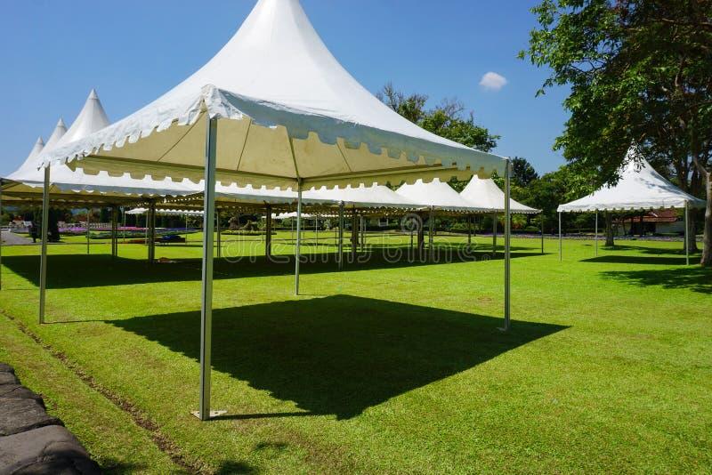 Tente blanche avec l'herbe verte sur le parc de jardin avec le hangar - photo Indonésie Bogor photographie stock