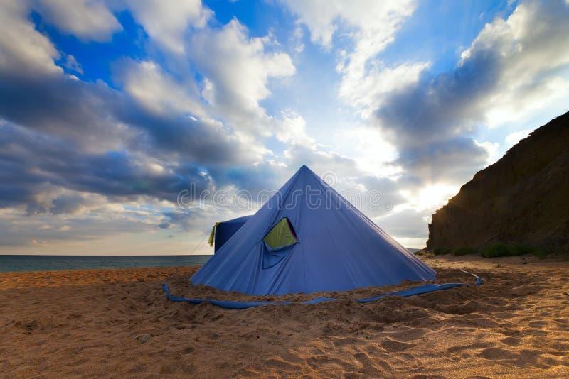 Tente conique sur la plage d'été et le ciel bleu avec des nuages photographie stock