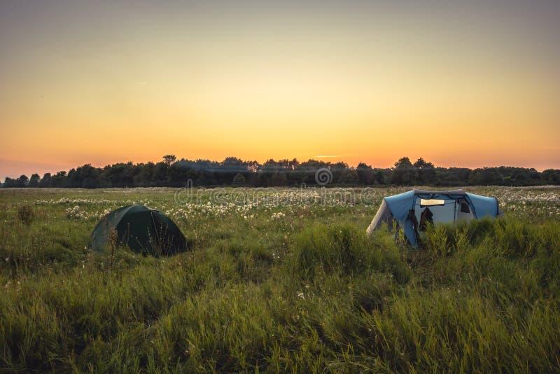 Tente de camping sur le champ rural d'été avec la forêt sur le fond et ciel orange de coucher du soleil pendant des vacances de c image libre de droits