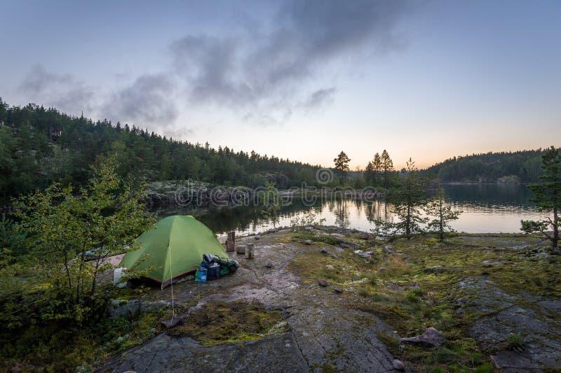 Tente de touristes dans le coucher du soleil à l'île rocheuse du lac Ladoga images stock