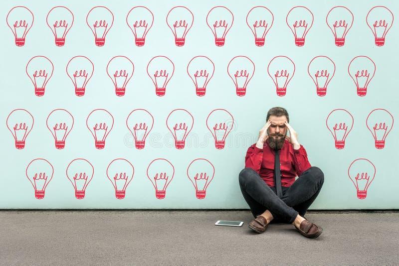 Tente encontrar a ideia ou a resolução de problemas Homem de negócio farpado pensativo novo na camisa vermelha que senta-se no fotografia de stock