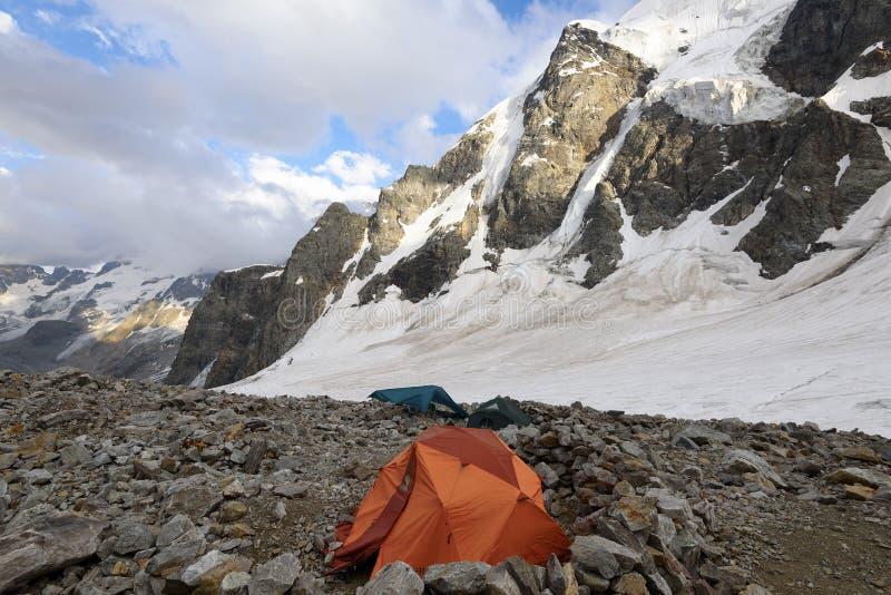 Download Tente Orange Parmi Des Pierres Dans Le Camp Des Montagnes Contre Des Montagnes Et Photo stock - Image du emplacements, aventure: 76089790