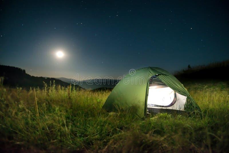 Tente verte dans les montagnes la nuit photographie stock libre de droits