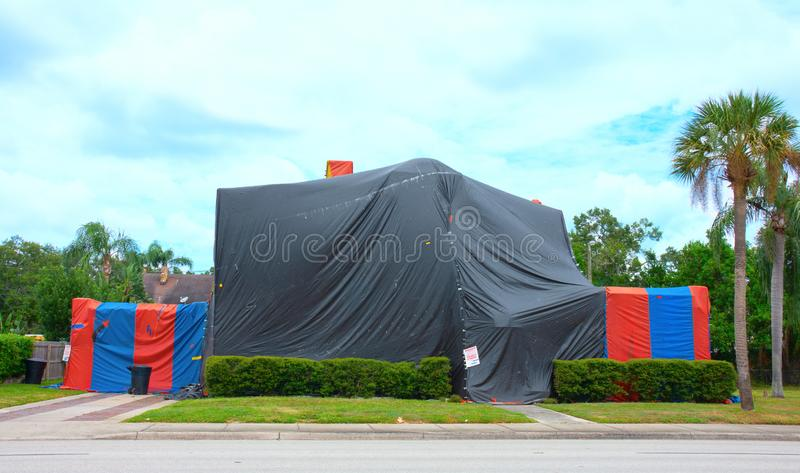 Tented large two story house that is being treated to kill termites and other bugs with structural fumigation. Tented large two story house with palm trees in royalty free stock image