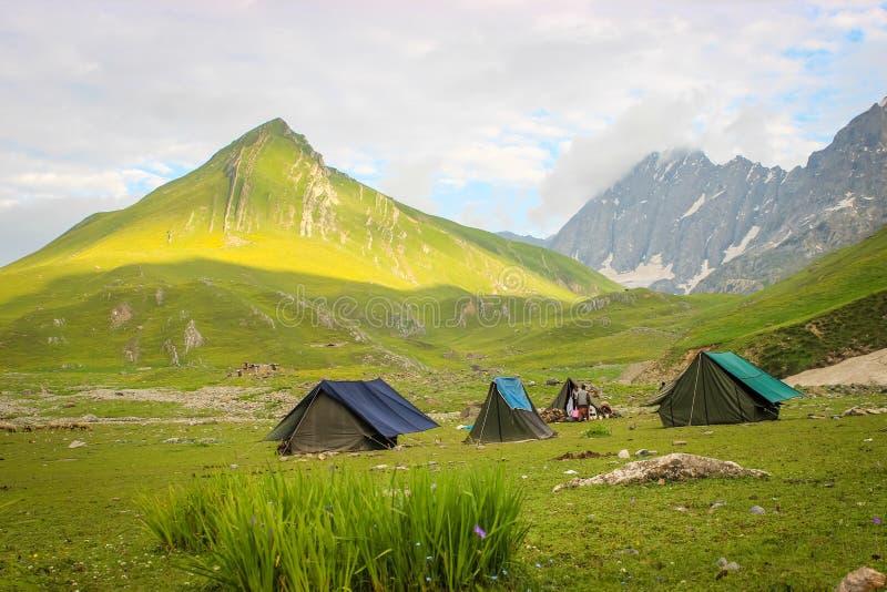 Tentes érigées sur l'itinéraire de trekking au lac Gangabal au Cachemire Lumière de matin de lever de soleil frappant la montagne photographie stock