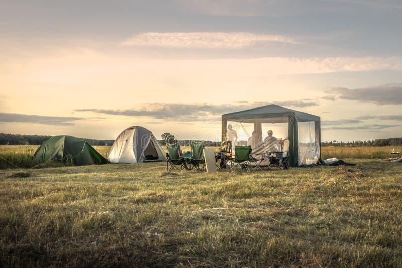 Tentes de camping de camping sur le ciel de coucher du soleil de champ d'été pendant des vacances de camping photographie stock libre de droits