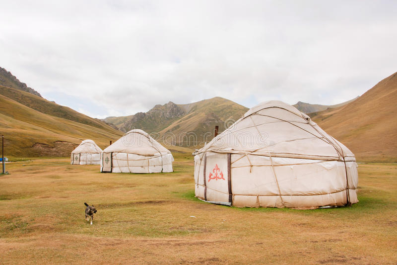 Tentes Yurts - maisons des personnes asiatiques nomades locales dans une vallée de montagne d'herbe sèche images stock
