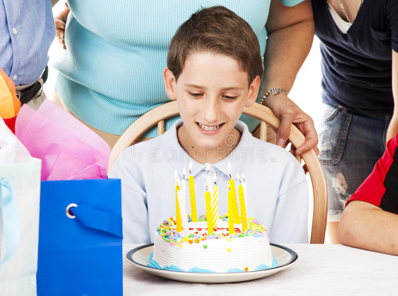 Tenth Birthday Celebration. Little boy looking at the candles on his birthday cake - ten and one to grow on stock image